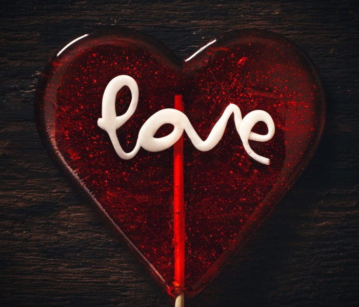 Red heart-shaped lollipop with word LOVE in icing.